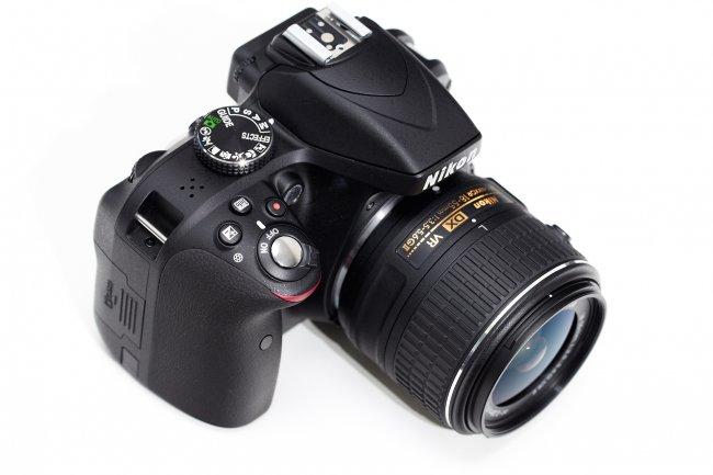 Nikon D3300 + 18-55 mm VR II: Frontansicht mit Moduswahlrad, Auslöser und Blitz